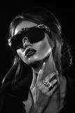 Портрет студии привлекательной женщины нося необыкновенные солнечные очки Стоковая Фотография