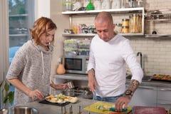 Портрет супруга и жены cuting сыр в кухне Стоковое фото RF