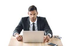 Портрет сфокусированного бизнесмена работая на компьтер-книжке на рабочем месте Стоковое фото RF