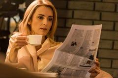 портрет сфокусированной коммерсантки с газетой чтения чашки кофе стоковые изображения
