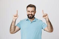 Портрет счастливого бородатого кавказского парня указывая вверх с обеими руками и усмехаясь жизнерадостно, стоя над серым цветом стоковые изображения rf