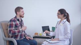 Портрет счастливого доктора диетолога, усмехаясь женщина диетврача делает план диеты для мужского пациента во время консультации акции видеоматериалы