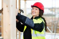 Портрет счастливого женского плотника бить молотком древесину молотком Стоковые Изображения RF