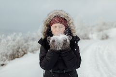 Портрет счастливого женского туриста дуя с снега от ее Хана Стоковые Фото
