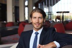 Портрет счастливого молодого бизнесмена сидя на софе в лобби гостиницы Стоковые Фотографии RF