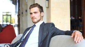 Портрет счастливого молодого бизнесмена сидя на софе в лобби гостиницы Стоковое Фото