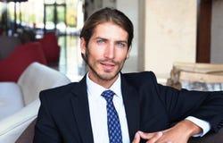Портрет счастливого молодого бизнесмена сидя на софе в лобби гостиницы Стоковые Изображения
