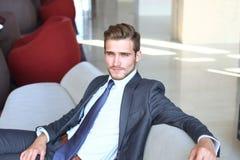 Портрет счастливого молодого бизнесмена сидя на софе в лобби гостиницы Стоковое фото RF