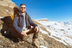 Портрет счастливого смеясь над путешественника битника с бородой в солнечных очках сидит на природе Стоковые Изображения