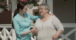 Портрет счастливого старшего терпеливого пенсионера и молодой медсестры усмехаясь Outdoors на съемке дома престарелых на красной  видеоматериал