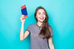 Портрет счастливого усмехаясь паспорта удерживания маленькой девочки и билетов путешествовать над голубой предпосылкой стоковое изображение