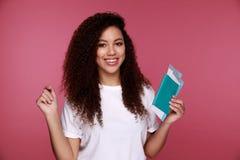 Портрет счастливого усмехаясь паспорта удерживания маленькой девочки и билетов путешествовать изолированных над предпосылкой стоковое фото rf