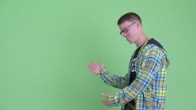 Портрет счастливого человека болвана показывая что-то и давая большие пальцы руки вверх акции видеоматериалы