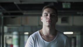 Портрет счастливого человека в белой футболке идя в подземную стоянку движение медленное сток-видео
