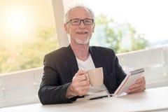 Портрет счастливого человека держа тетрадь и чашку кофе, световой эффект Стоковые Изображения
