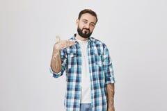Портрет счастливого эмотивного бородатого европейца, жестикулируя с одной рукой действуя как рэппер или dj, стоя над серым цветом стоковое изображение