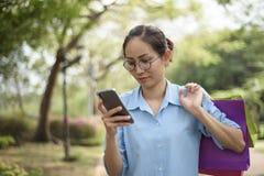 Портрет счастливой азиатской молодой женщины держа хозяйственные сумки и Стоковые Фотографии RF