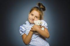 Портрет счастливой девушки играя с плюшевым медвежонком на сером цвете стоковая фотография