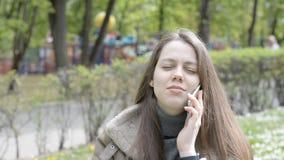 Портрет счастливой девушки красивый говоря на сотовом телефоне и усмехаться видеоматериал