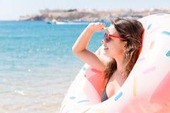 Портрет счастливой девушки смотря через раздувное пребывание кольца на пляже моря Летние отпуска и концепция каникул стоковое фото