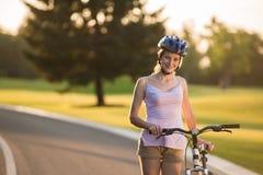Портрет счастливой девушки с велосипедом outdoors Стоковые Фотографии RF