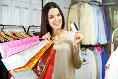 Портрет счастливой девушки с хозяйственными сумками и кредитной карточки в магазине одежды Стоковые Изображения RF