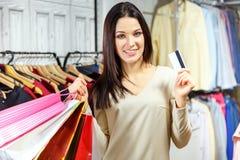 Портрет счастливой девушки с хозяйственными сумками и кредитной карточки в магазине одежды Стоковая Фотография RF