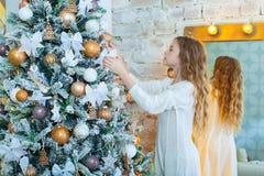 Портрет счастливой девушки украшая рождественскую елку Стоковая Фотография