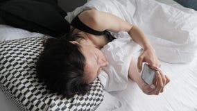 Портрет счастливой женщины в ее прекрасной спальне кладя вниз на белую кровать отправляя SMS на смартфоне Технология, интернет видеоматериал