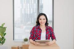 Портрет счастливой женщины используя цифровую таблетку во время moving дома Стоковая Фотография