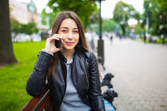 Портрет счастливой женщины сидя на стенде и говоря на телефоне outdoors Стоковая Фотография RF