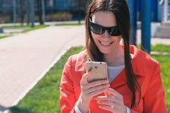 Портрет счастливой женщины oung в красном пальто ждет кто-то и проверяет ее телефон, отправляя СМС стоковая фотография rf