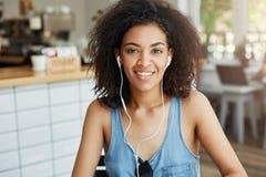 Портрет счастливой красивой африканской девушки в наушниках усмехаясь смотрящ камеру сидя в кафе Стоковая Фотография RF