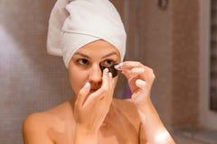 Портрет счастливой красивой девушки кладя на заплаты под глазами в bathroom r стоковые фото