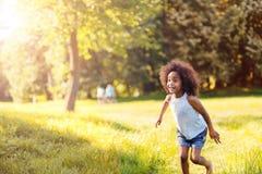 Портрет счастливой маленькой девочки бежать на земле травы Стоковое Фото