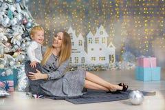 Портрет счастливой матери и прелестный младенец празднуют рождество Праздники ` s Нового Года Малыш с festively украшенной мамой  стоковые изображения