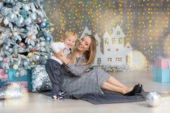 Портрет счастливой матери и прелестный младенец празднуют рождество Праздники ` s Нового Года Малыш с festively украшенной мамой  стоковое изображение
