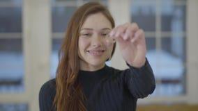 Портрет счастливой милой усмехаясь женщины показывая ключи купленных нового дома или квартиры к камере Фокус акции видеоматериалы