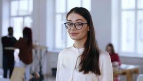 Портрет счастливой молодой бизнес-леди босса брюнета в eyeglasses представляя, усмехаясь на камере на современном ультрамодном оф сток-видео