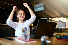 Портрет счастливой молодой бизнес-леди празднуя успех с оружиями вверх перед компьтер-книжкой Женщина смешанной гонки выигранная  стоковые изображения