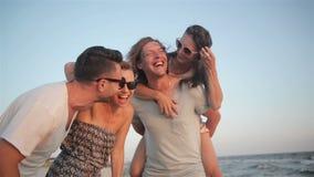 Портрет счастливой молодой группы людей наслаждаясь праздником пляжа 4 друз смеются над около моря во время лета сток-видео