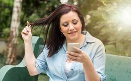 Портрет счастливой молодой женщины используя ее мобильный телефон, световой эффект Стоковое Изображение