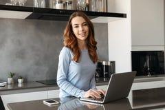 Портрет счастливой молодой женщины используя портативный компьютер Стоковое Фото