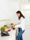 Портрет счастливой молодой женщины подготовляя еду i Стоковая Фотография RF