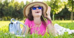 Портрет счастливой молодой женщины при шляпа и солнечные очки лежа в парке на пикнике Стоковое Изображение RF