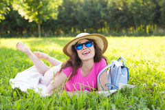 Портрет счастливой молодой женщины при шляпа и солнечные очки лежа в парке на пикнике Стоковое фото RF