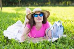Портрет счастливой молодой женщины при шляпа и солнечные очки лежа в парке на пикнике Стоковое Изображение