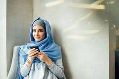 Портрет счастливой мусульманской женщины используя мобильный телефон пока сидящ на кресле стоковая фотография rf