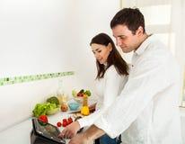 Портрет счастливой пары подготовляя еду Стоковая Фотография