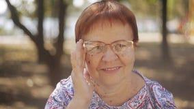 Портрет счастливой пожилой женщины в парке смеясь над наслаждающся выбытыми стеклами образа жизни нося сток-видео